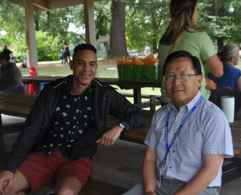 Two people facing the camera are sitting in an outdoor covered area. Both are smiling.