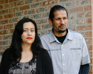 Two people stand together with a brick wall behind them.